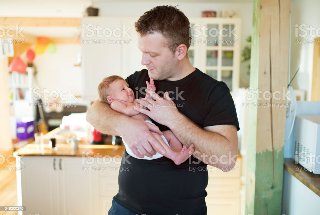 Young father with his newborn baby daughter in his arms stock photo