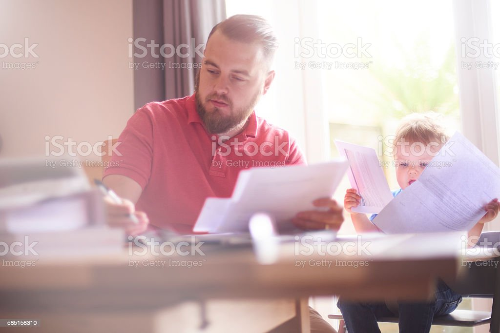 Young father working from home with toddler stock photo