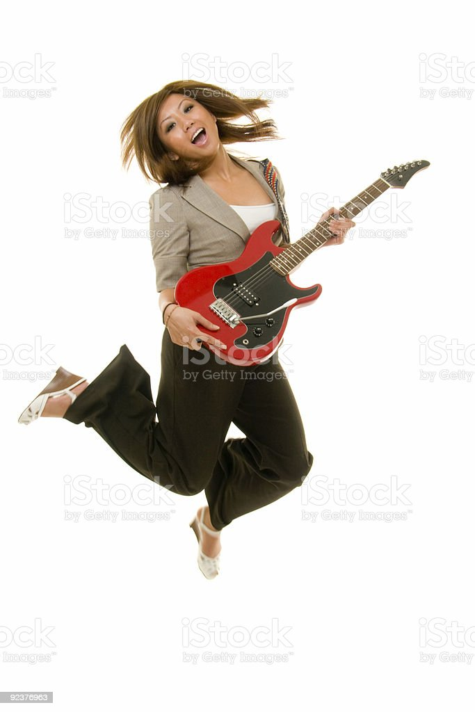 Young Female Adult Jumping While Playing Guitar royalty-free stock photo