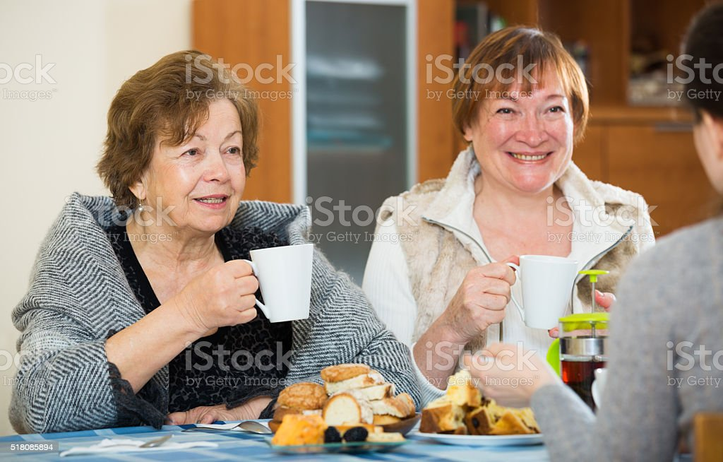 Young female and mature women drinking tea and talking stock photo