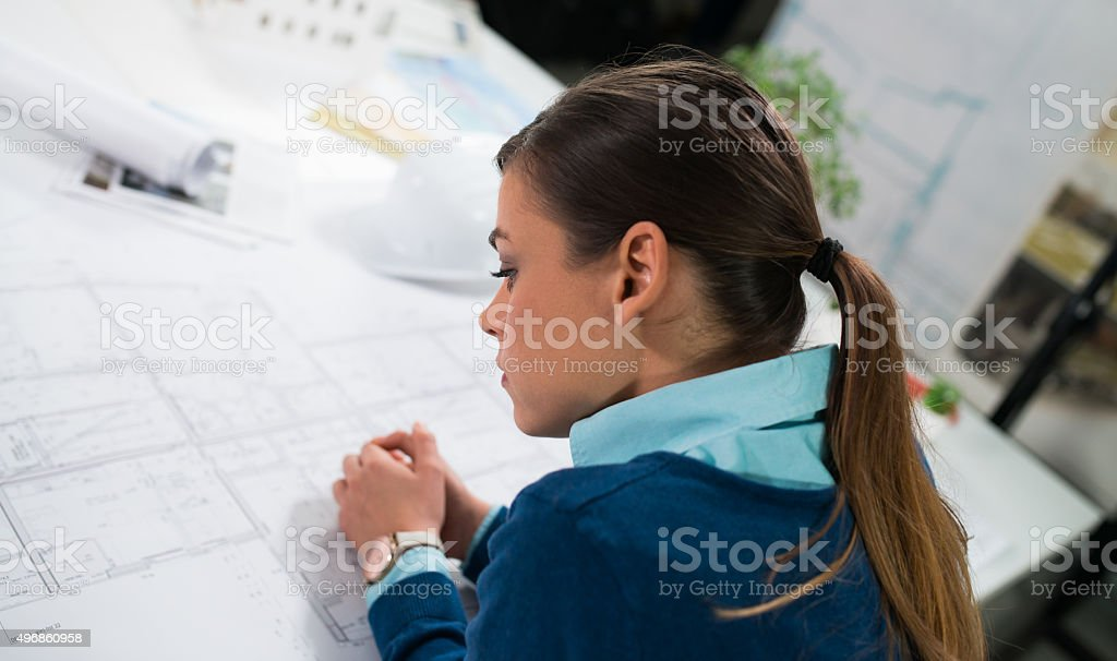 Young Female Architect Looking At Blueprint stock photo