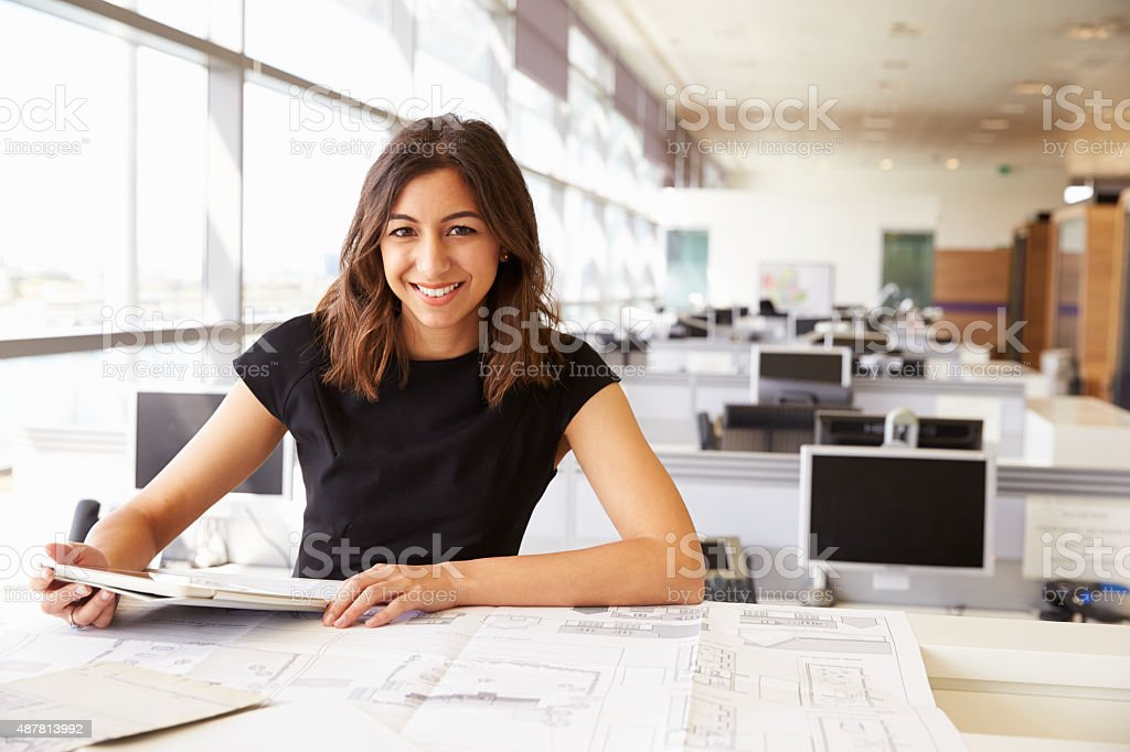 Young female architect working with computer and blueprints stock photo