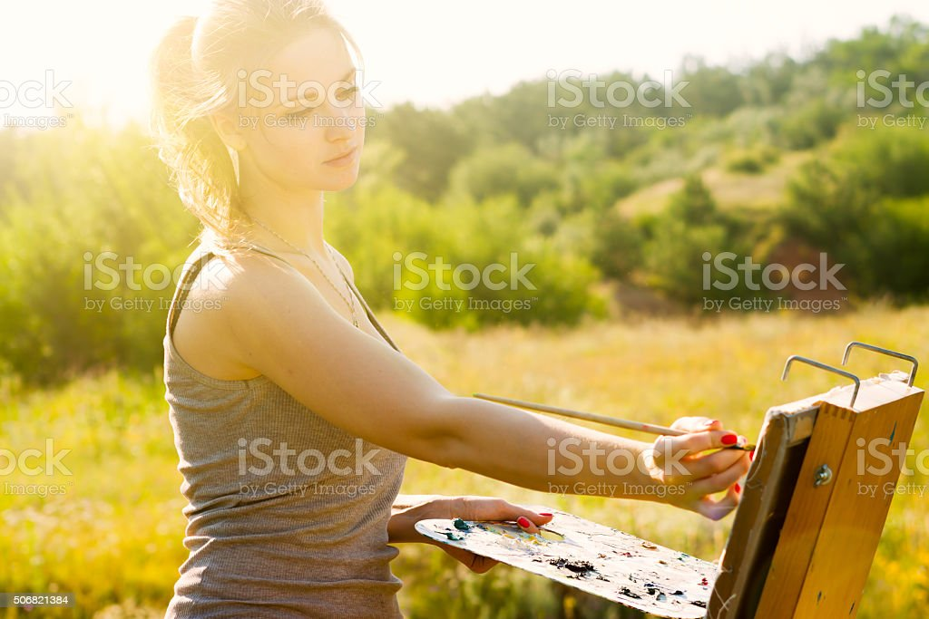Young female artist painting a picture on canvas stock photo