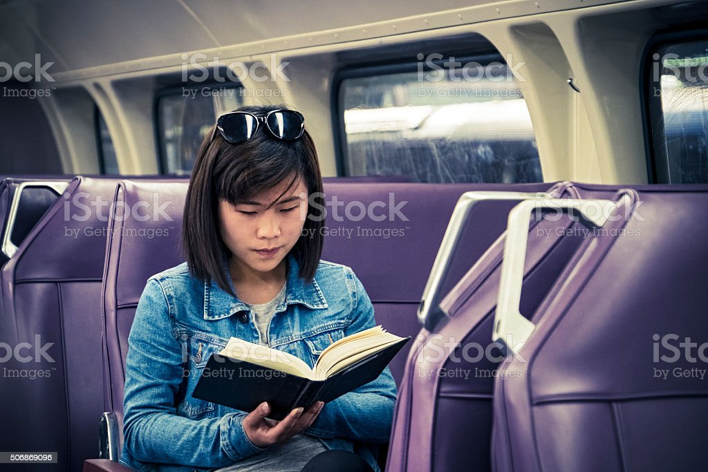 Young female Asian student reading textbook in train carriage stock photo