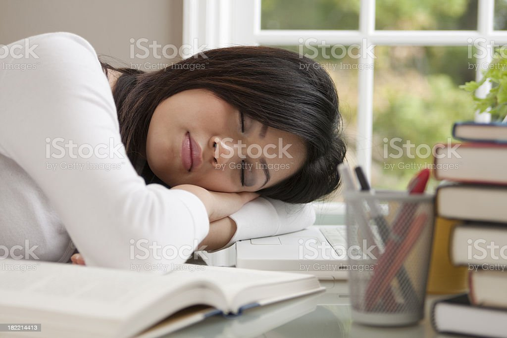 Young Female Asian Student Sleeping or Napping on Her Desk royalty-free stock photo
