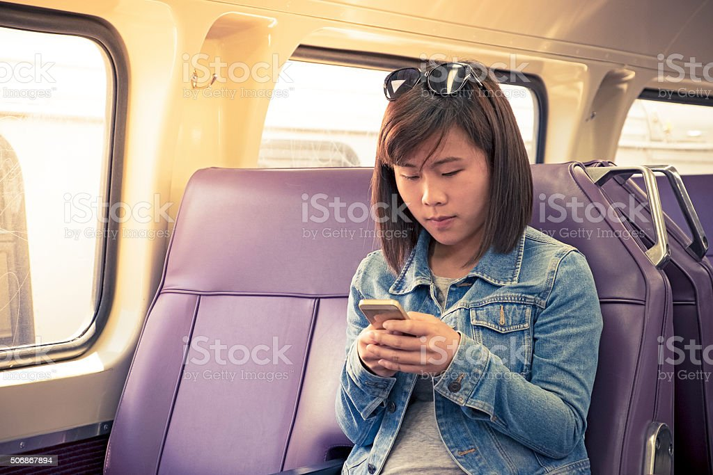 Young female Asian student using smartphone in train carriage stock photo
