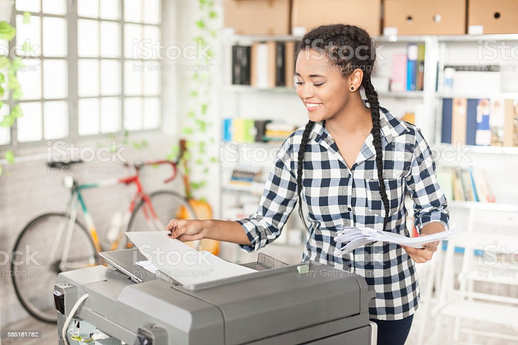 Young female assistant using copy machine at workplace stock photo