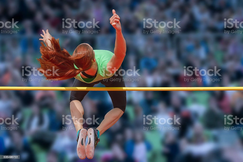 Young female athlete at high jump stock photo