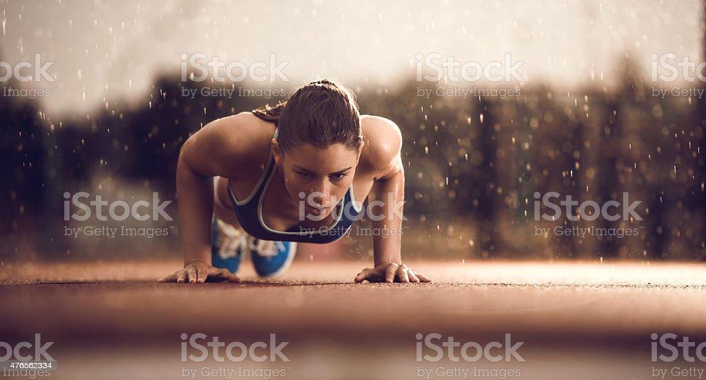 Young female athlete doing push-ups on a rain. stock photo