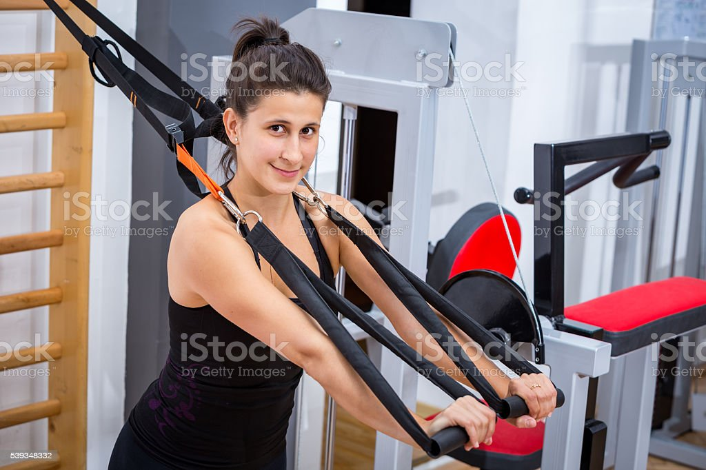 Young female athlete girl training her pecs, with TRX suspension stock photo