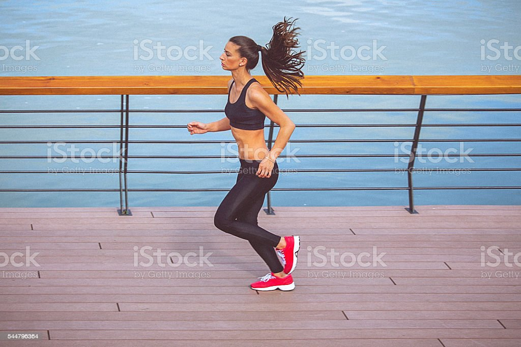 Young female athlete jogging on the waterfront stock photo