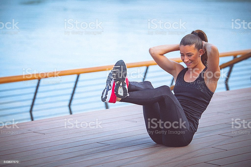 Young female athlete performs ab crunches outdoors stock photo