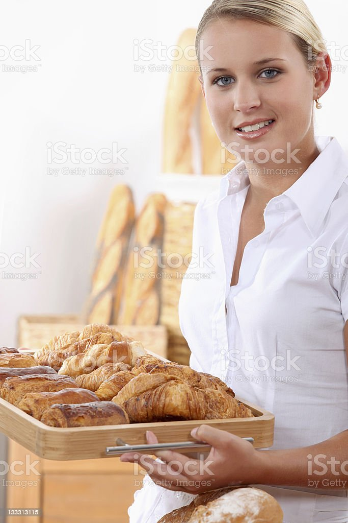 Young female baker with croissants and pain au chocolats royalty-free stock photo