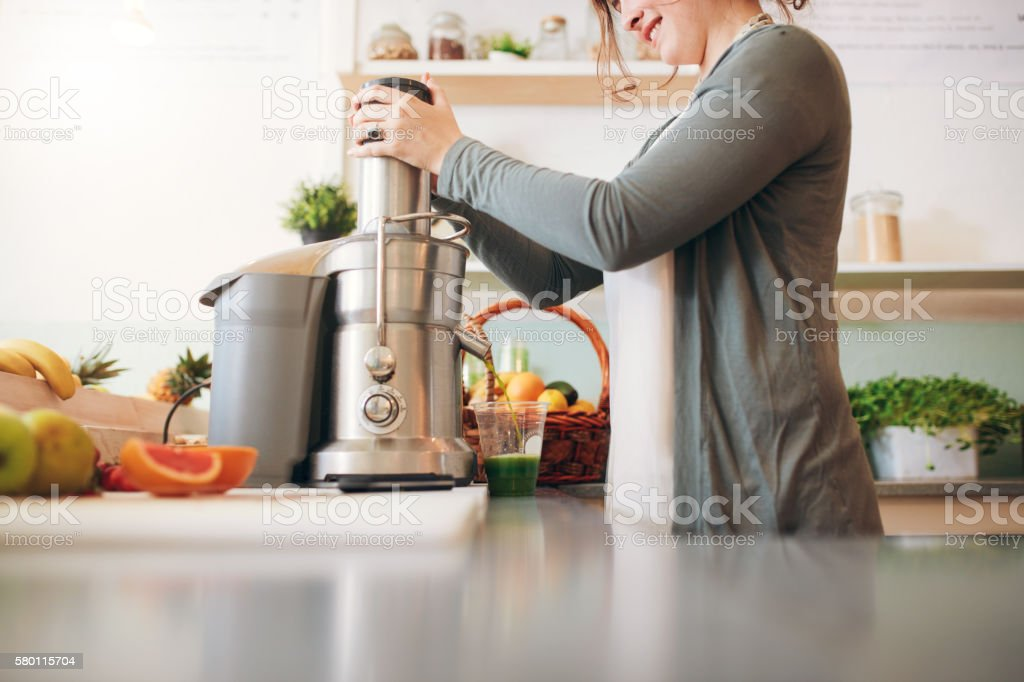 Young female bar employee making fruit juice stock photo