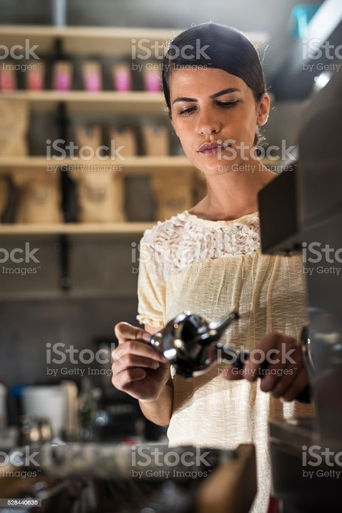 Young female barista making coffee in a cafe. stock photo