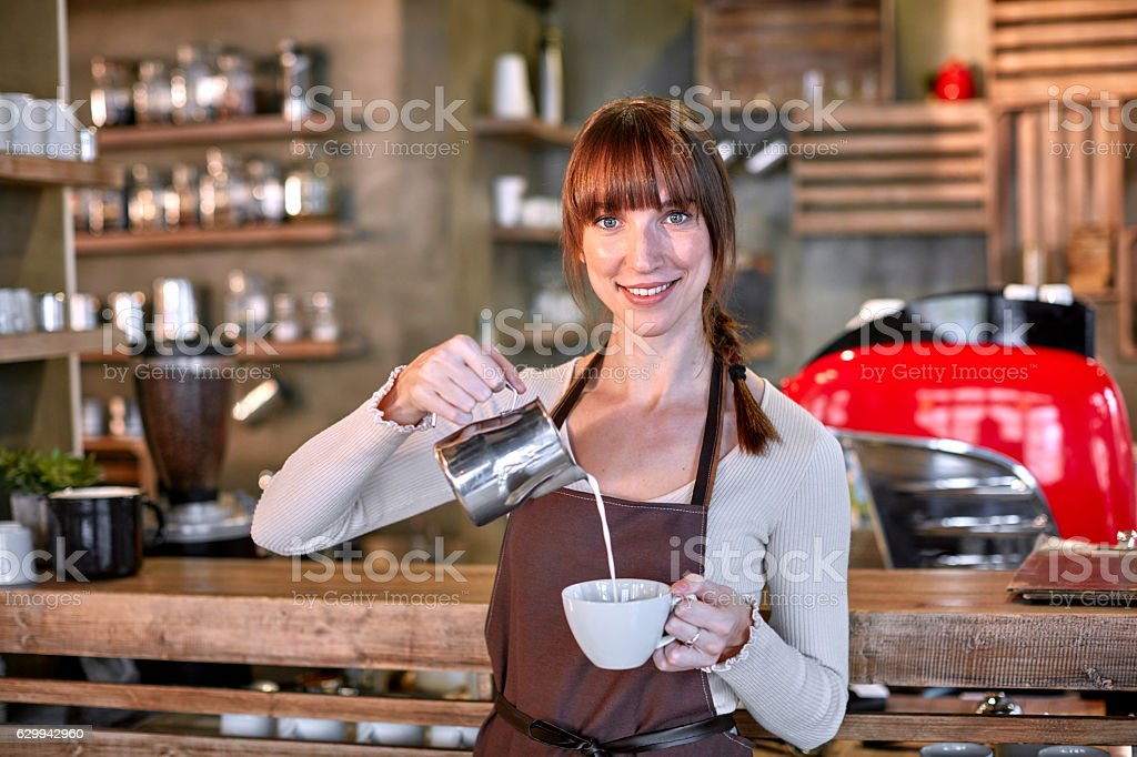 Young female barista pouring milk in coffee cup in cafe stock photo