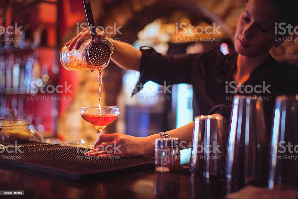 Young female bartender pouring cocktails in a cocktail bar stock photo