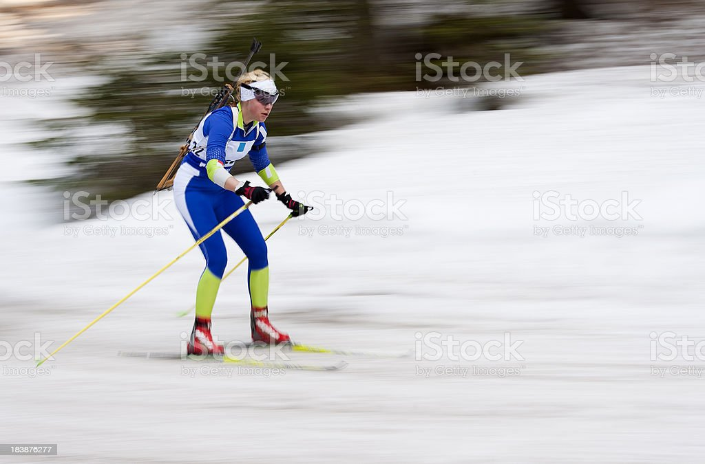 Young female biathlon competitor at downhill stock photo