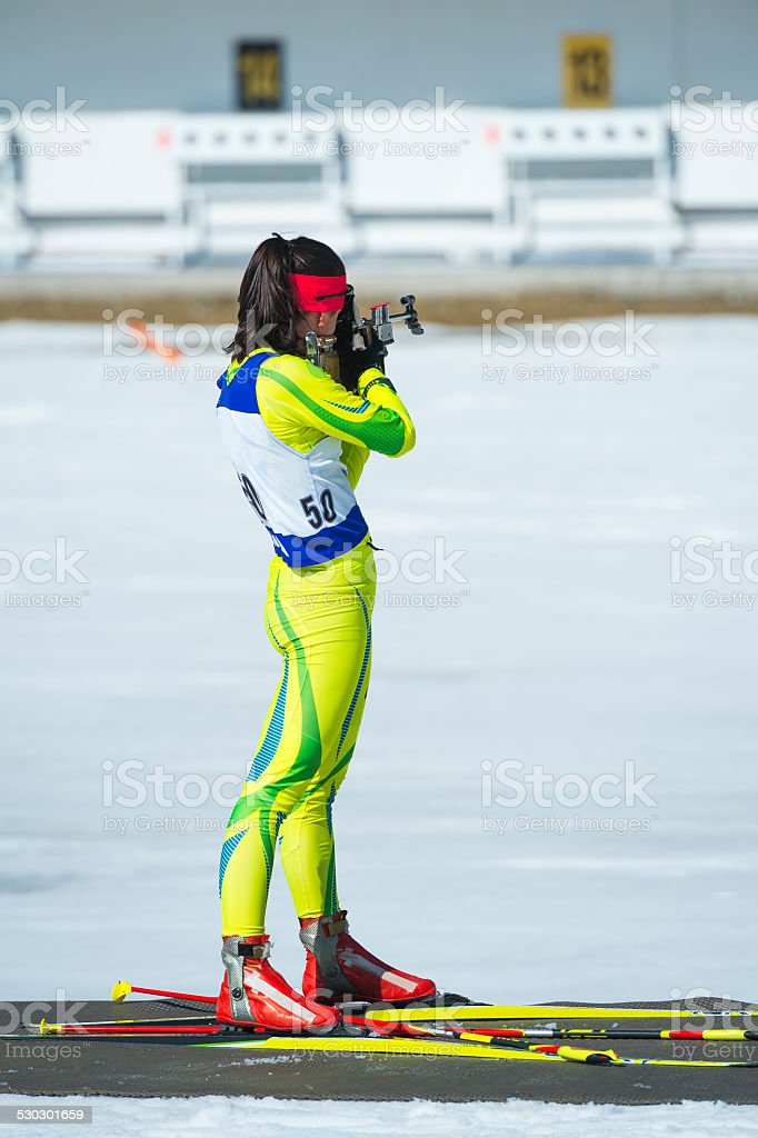 Young female biathlon competitor at shooting range stock photo