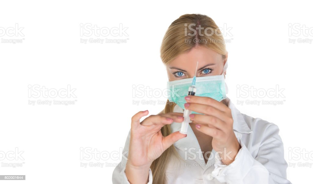 Young female blonde doctor with blue eyes, posing with vaccine syringe stock photo