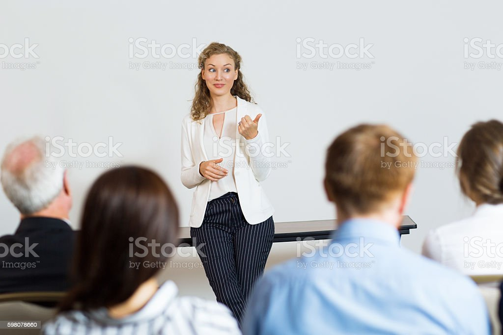Young Female Business Coach talking with Audience at Conference stock photo