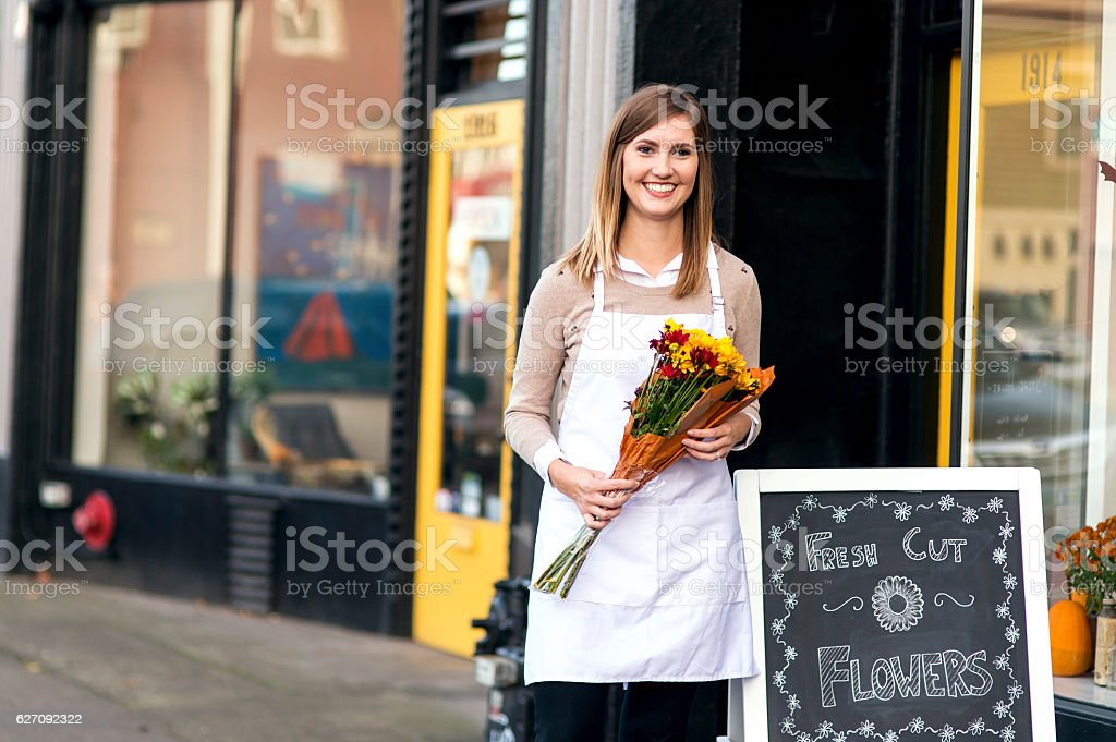 Young female business owner holding flowers outside flower shop stock photo