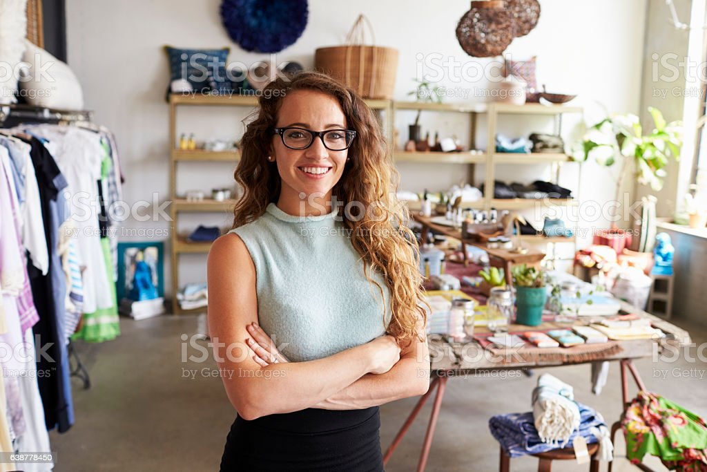 Young female business owner in a clothes shop, portrait stock photo