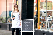 Young female business owner standing outside her salon shop