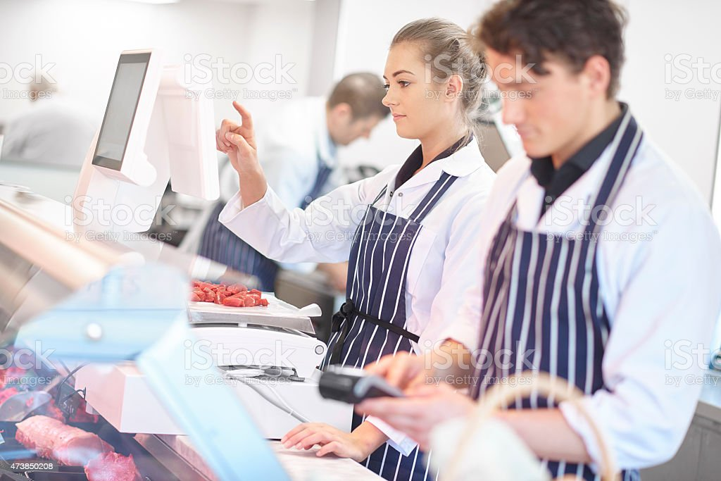 young female butcher portrait in a busy butcher's shop. stock photo