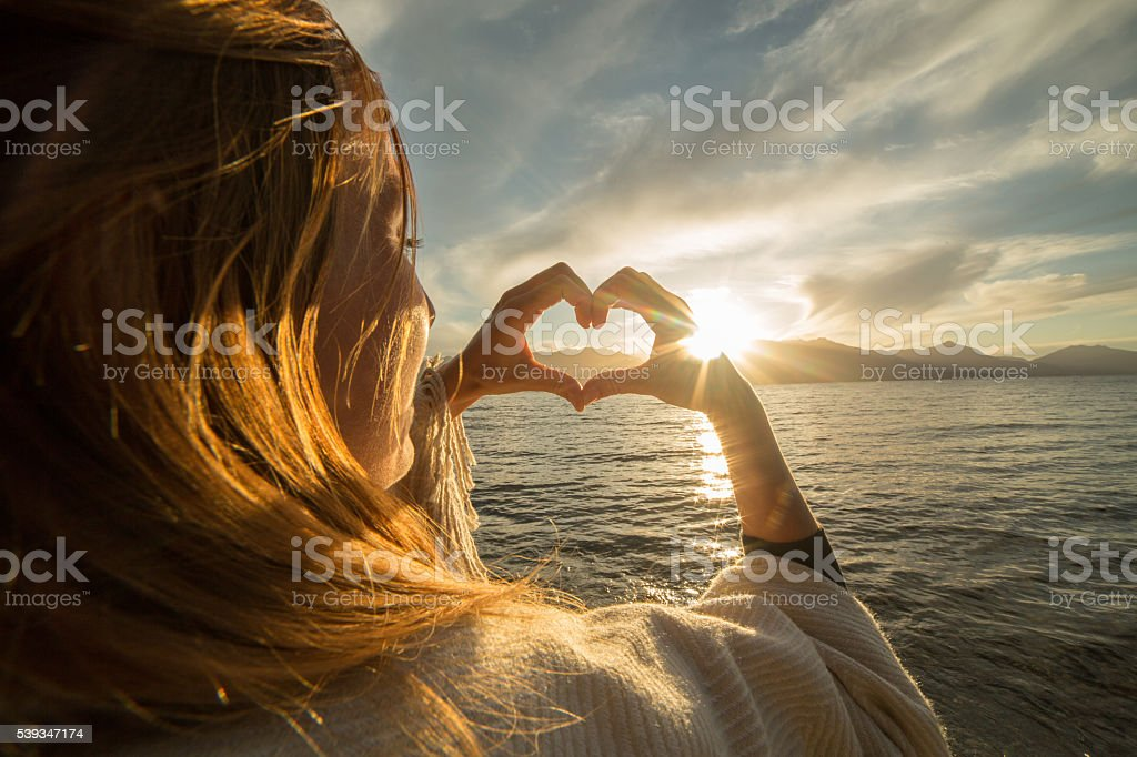 Young female by the lake making heart shape finger frame stock photo