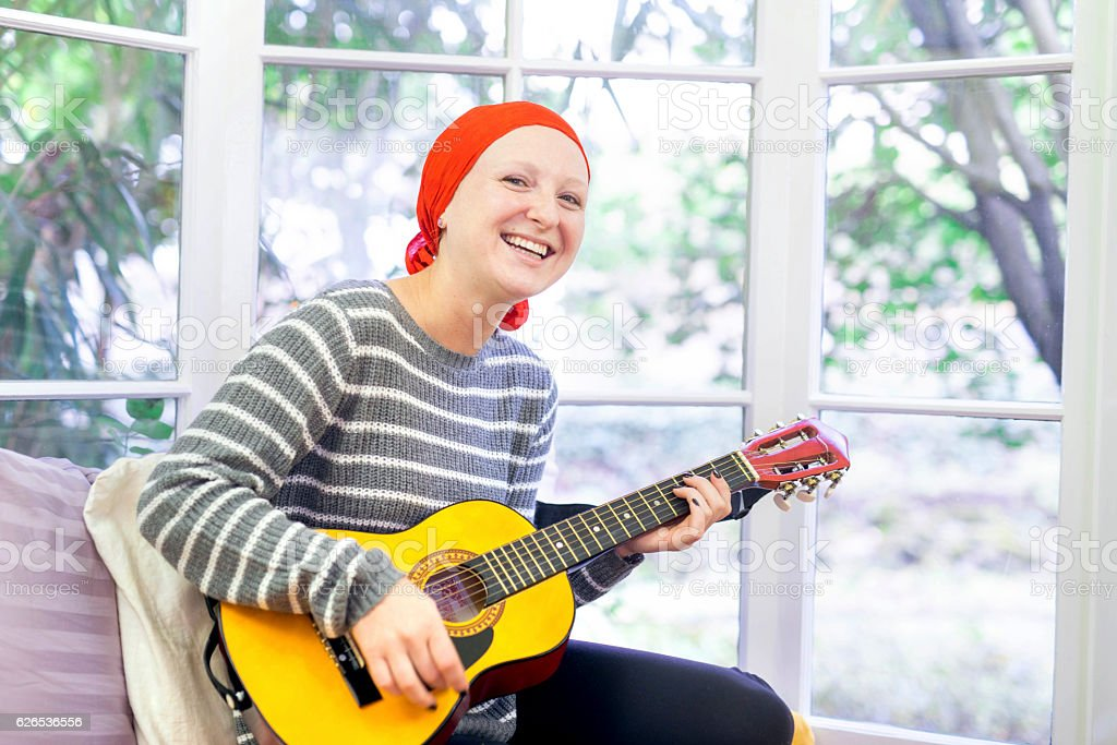Young female cancer patient feeling happy while playing the guitar stock photo