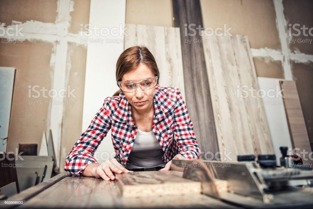 Young female carpenter using a circular saw stock photo