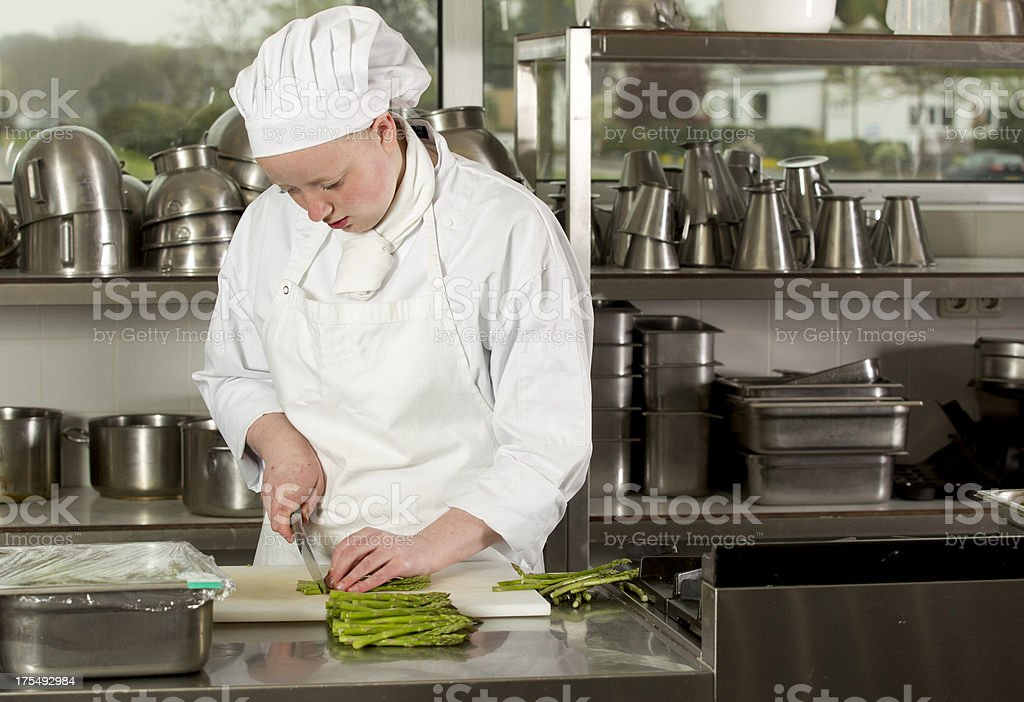 Young Female Chef Cutting Asparagus royalty-free stock photo
