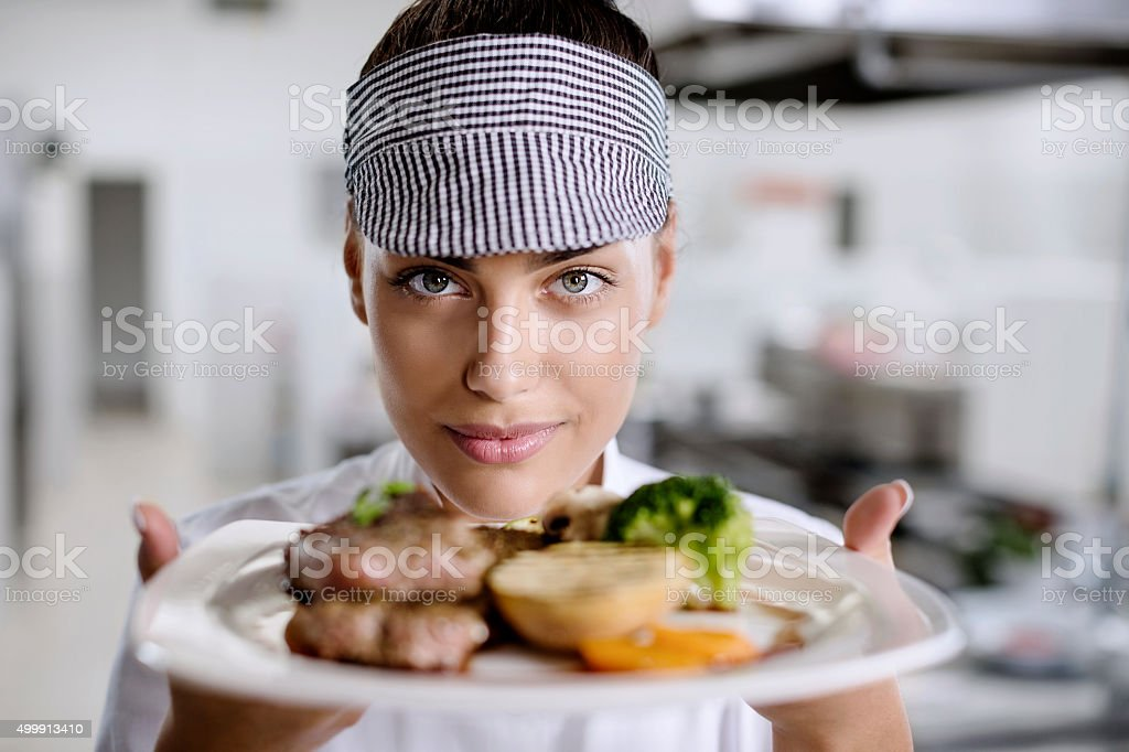 Young female chef presenting food stock photo