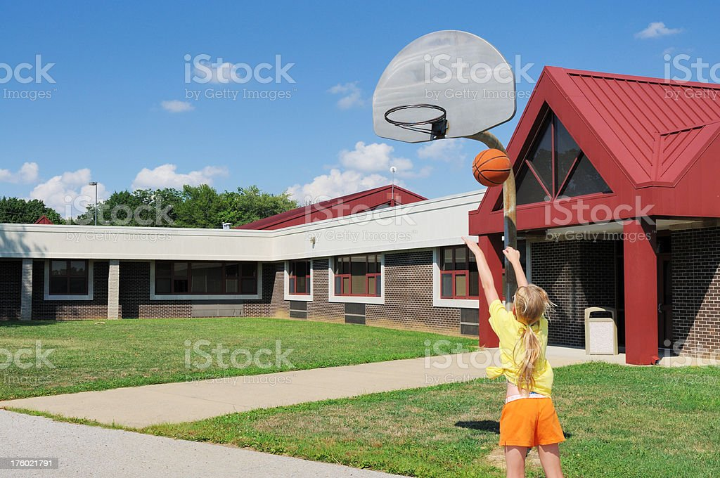 Young Female Child Shooting Basketball in School Playground stock photo