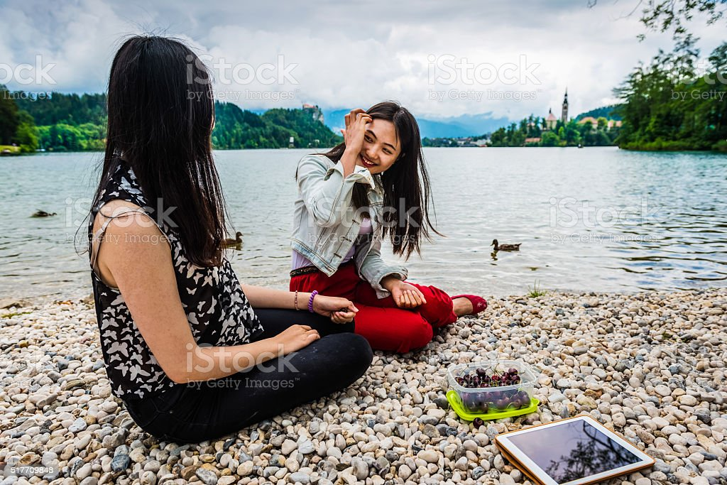 Young Female Chinese Friends Eating Cherries, Bled Lake, Slovenia, Europe stock photo