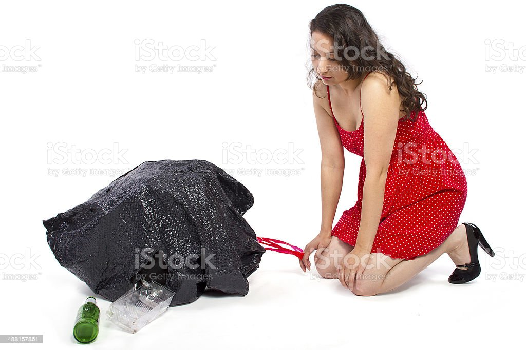 Young Female Cleaning a Messy Broken Trash Bag stock photo