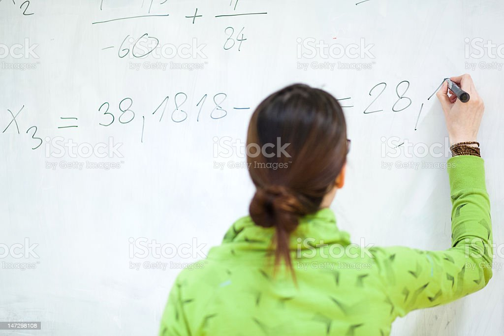 young female college student in front of a whiteboard stock photo