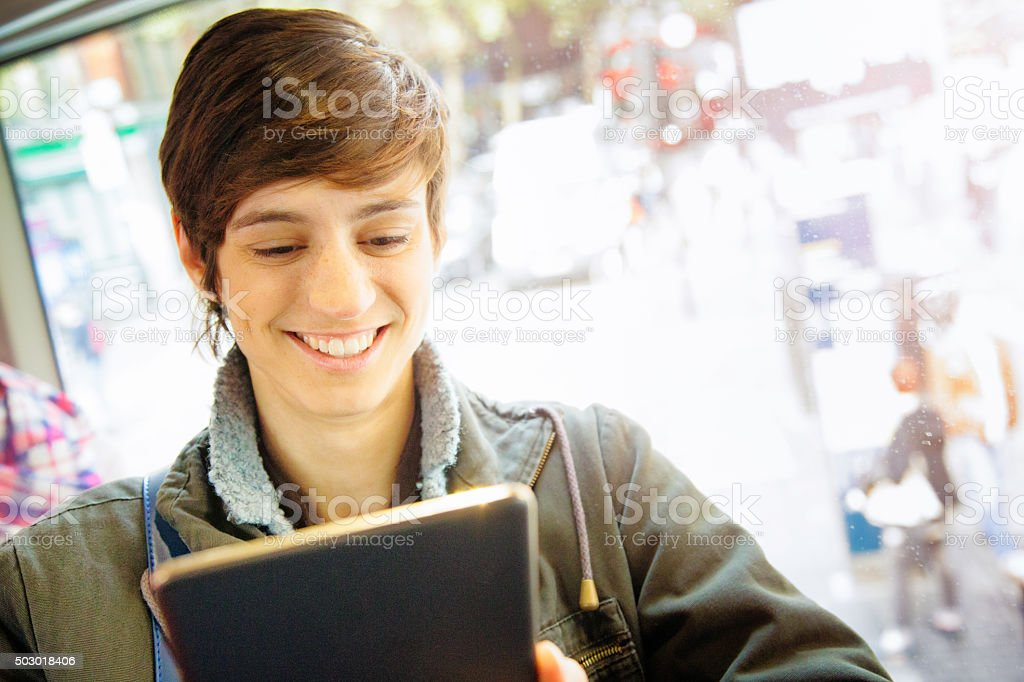 Young female commuter enjoying entertainment on tablet stock photo