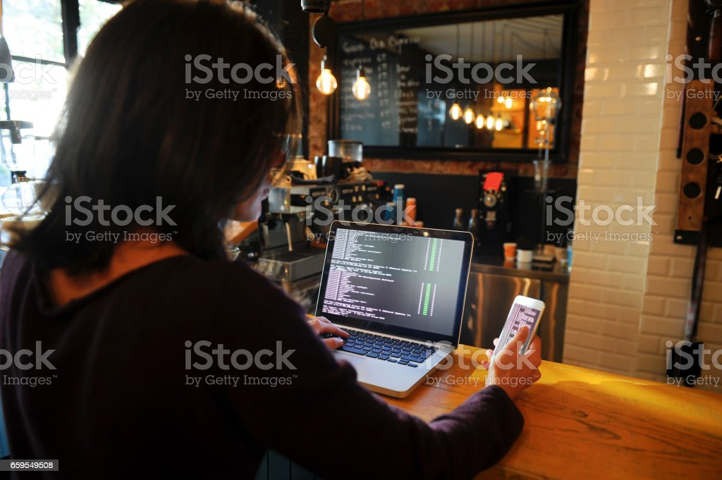 Young female computer programmer working on computer