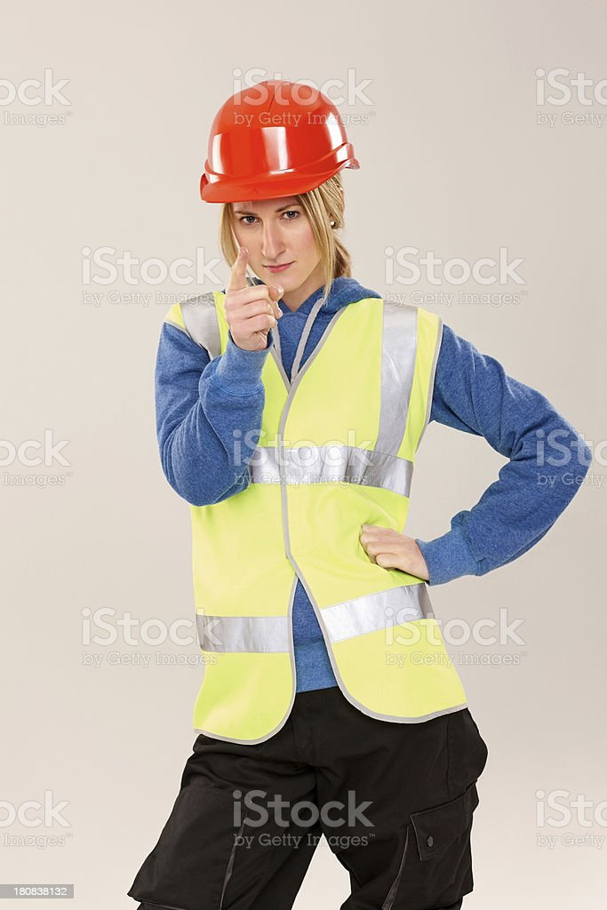 Young female construction worker pointing at you royalty-free stock photo