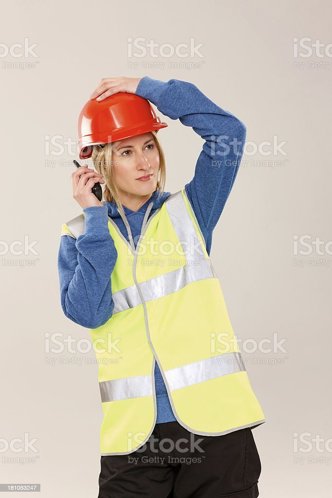Young female construction worker talking on walkie talkie royalty-free stock photo
