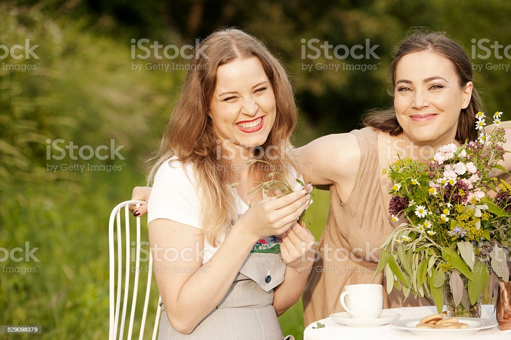 Young Female Couple Enjoying Afternoon Tea on their Garden stock photo