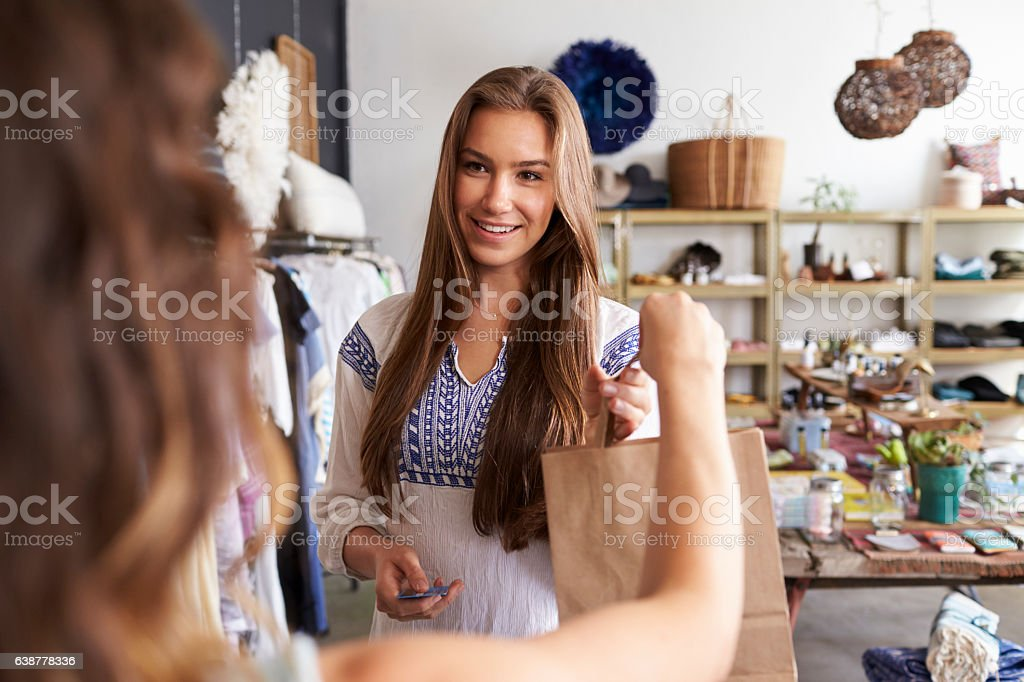 Young female customer takes bag from assistant in a boutique stock photo