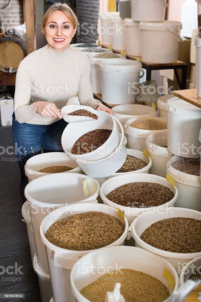 Young  female customer taking bird forage with scoop from bucket stock photo