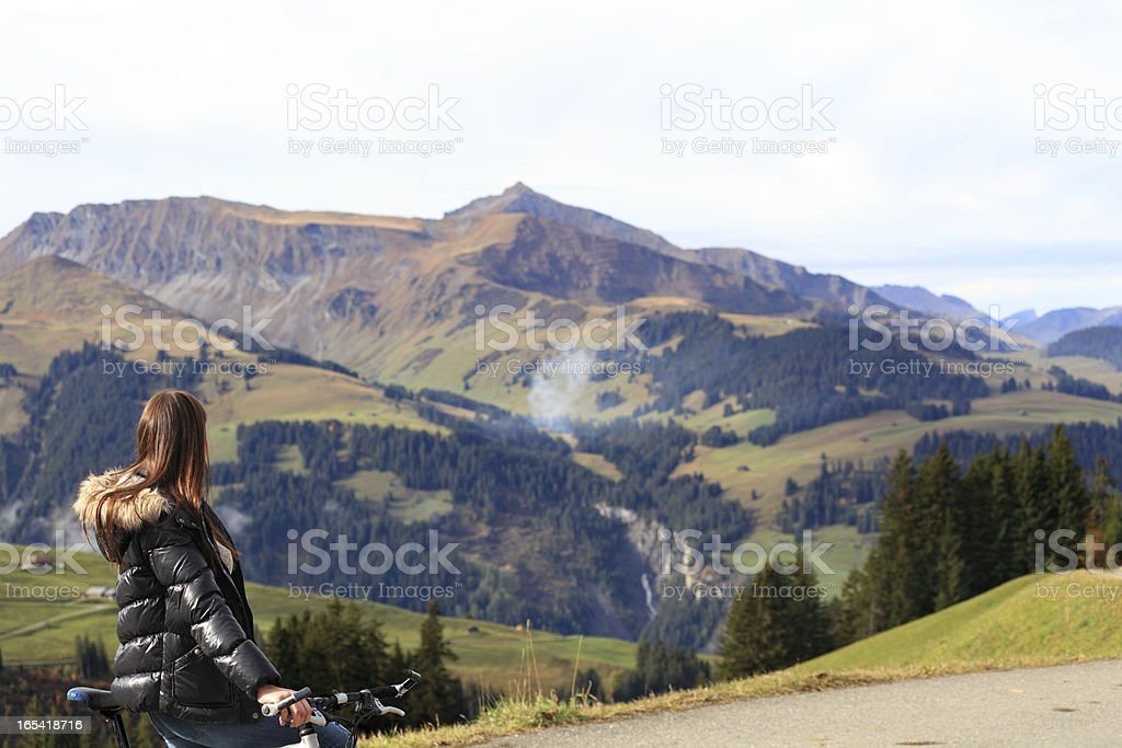 young female cyclist admires view in Swiss Alps royalty-free stock photo
