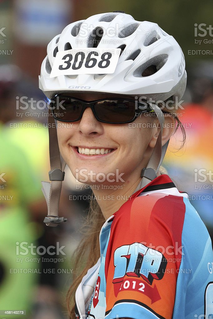Young female cyclist smiling while looking at the camera royalty-free stock photo