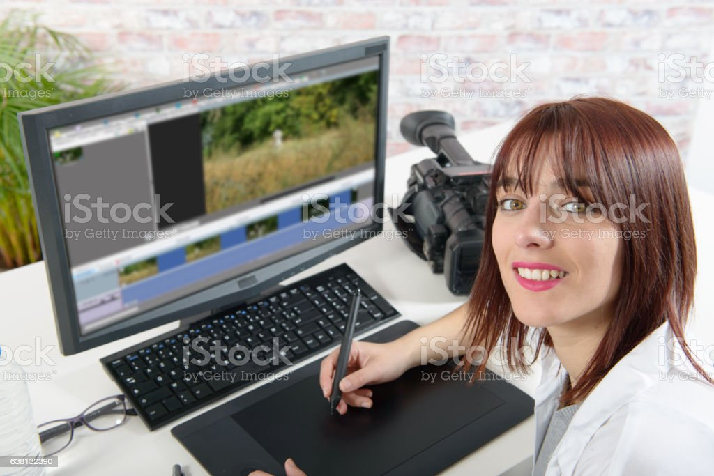 young female designer using computer for video editing stock photo
