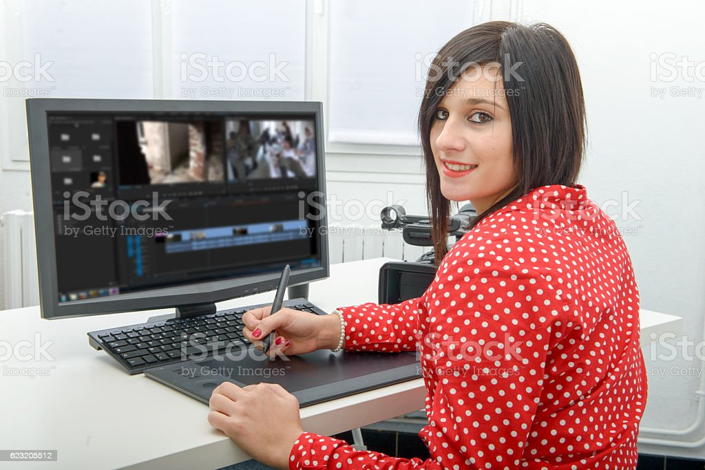 young female designer using graphics tablet for video editing stock photo