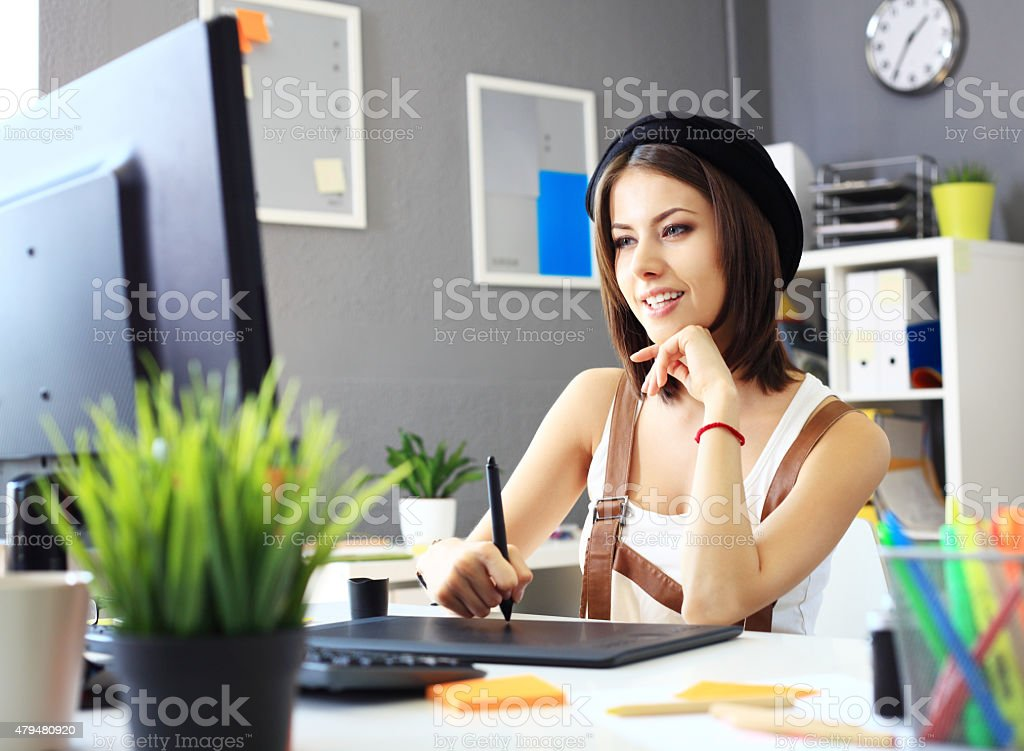 Young female designer using graphics tablet while working stock photo